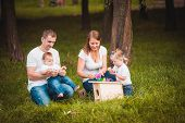 pic of nesting box  - Happy family with nesting box and colorful paints in green summer forest - JPG