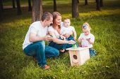 image of nesting box  - Happy family with nesting box and colorful paints in green summer forest - JPG