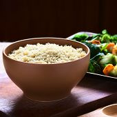 stock photo of quinoa  - Cooked white quinoa seeds in bowl with cooked vegetables in the back photographed with natural light  - JPG