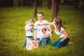 stock photo of nesting box  - Happy family with nesting box and colorful paints in green summer forest - JPG