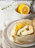 picture of cod  - Cod fillets  baked in parchment paper with slices of lemon and a sprig of thyme on light dishes - JPG