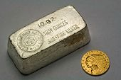 picture of coins  - Old silver bullion bar and 1911 United States five dollar Indian Head gold coin