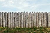 image of log fence  - A fence made of old cracked logs against the blue sky - JPG