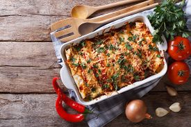 stock photo of enchiladas  - Mexican enchilada in a baking dish with the ingredients on the table - JPG