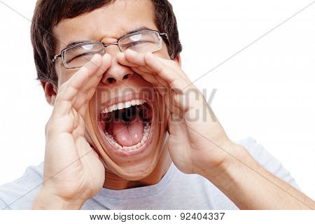Close up portrait of young man in glasses yelling with open hands on isolated white background