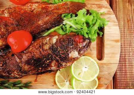 healthy food: two fried sea bass fish served with tomatoes and vegetables on big wooden board over table