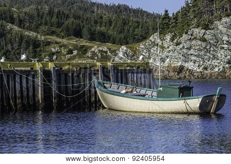 A small fishing boat tied up at the wharf in rural Newfoundland, Canada.