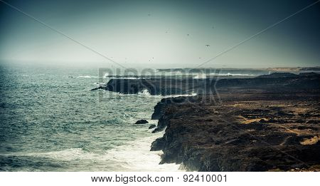 seawaves on a rocky shore at magnificent dusk