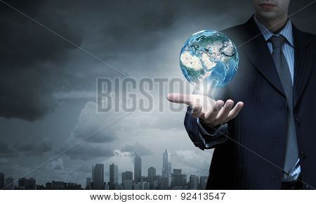Close up of businessman hand holding Earth planet. Elements of this image are furnished by NASA