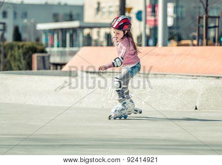 Little pretty girl on roller skates in helmet at a park
