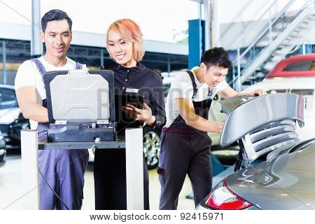Asian Chinese car mechanic team checking auto engine with diagnostics tool in his workshop