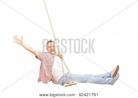 Studio shot of a young joyful man swinging on a swing and gesturing happiness isolated on white background