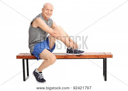 Studio shot of a cheerful senior in sportswear tying his shoelaces seated on a bench and looking at the camera isolated on white background