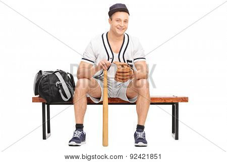 Young baseball player with a baseball glove and a bat sitting on bench and looking at the camera isolated on white background