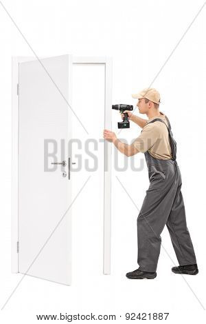 Full length portrait of a young manual worker installing a door with a hand drill isolated on white background