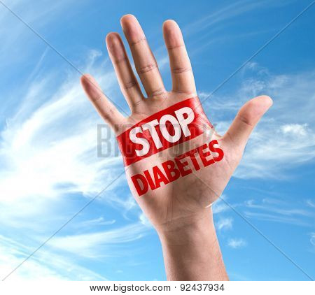 Open hand raised with the text: Stop Diabetes on sky background