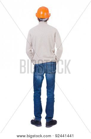 Backview of an engineer in construction helmet stands. Standing young guy. Rear view people collection.  Isolated over white background. Engineer in a warm jacket is folded his hands in his pockets.
