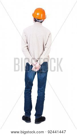 Backview of an engineer in construction helmet stands. Standing young guy. Rear view people collection. .  Isolated over white background. Engineer in a warm jacket is hands clasped behind his back.