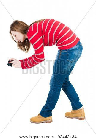 Back view of woman photographing.   girl photographer in jeans. Rear view people collection.  backside view of person.  Isolated over white background. Low leaning woman photographs.