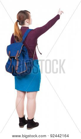 Back view of  pointing woman with backpack looking up. Standing young girl. Rear view people collection.  backside view of person.  The girl with big blue backpack shows thumb of his left hand.