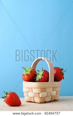 Strawberries In Small Basket Against Blue Background