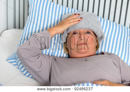 Sick Woman Lying On Bed With Towel On The Forehead