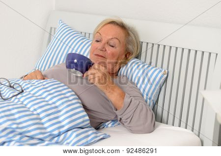 Adult Blond Woman On Her Bed Holding Her Cup