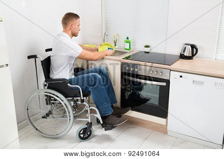 Man On Wheelchair Washing Dishes