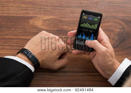 Businessman Checking Fitness Stats On Cellphone