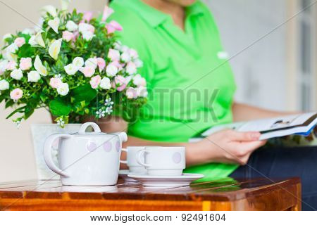 Young Woman Reading Magazine. White Porcelain Set For Tea Or Coffee And Vase Of Artificial Flowers O