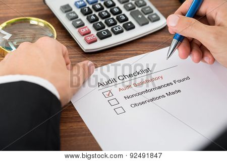 Person Filling Audit Checklist Form