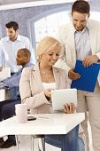 stock photo of work crew  - Young colleagues working together in office - JPG
