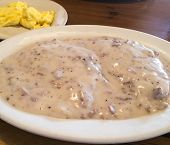 picture of hash  - corn beef hash gravy over toast with eggs in background - JPG