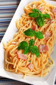 stock photo of carbonara  - Spaghetti carbonara decorated with fresh basil leaves - JPG