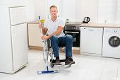 stock photo of handicapped  - Young Happy Handicapped Man On Wheelchair Mopping Floor In Kitchen - JPG