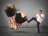 stock photo of high calorie foods  - Fat man kicks a high calorie sweet - JPG