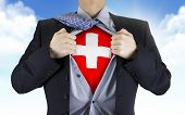 picture of flag confederate  - businessman showing Switzerland flag underneath his shirt over blue sky - JPG