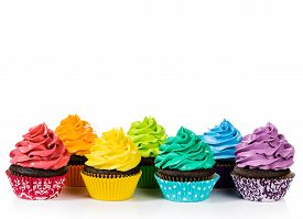 pic of icing  - Chocolate cupcakes in rows with colorful icing on a white background - JPG