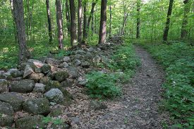 stock photo of old stone fence  - Hiking trail leading through and old stone fence - JPG