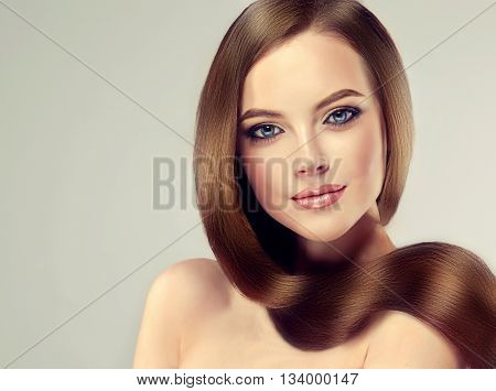 Beautiful brunette girl with long straight smooth hair . A woman with healthy straight hairstyle