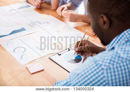 Be accurate. Pleasant involved busy man sitting at the table and thinking out the graph while working with his colleagues in the office