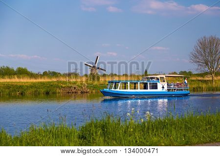 KINDERDIJK, NETHERLANDS - 7 MAY 2016: Windmills and touristic boat reflected in canals at iconic Kinderdijk site in the Netherlands