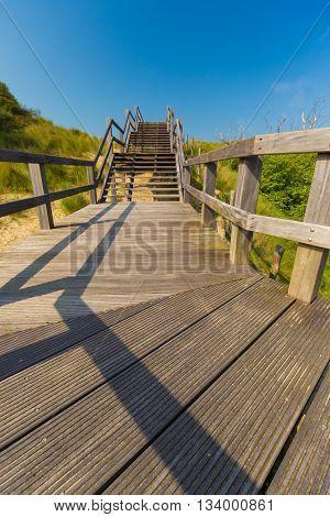 Wooden Staircase Going Into Blue Sky Among Dunes And High Grass, De Haan, Belgium