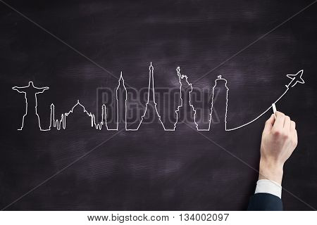 Travel concept with businessperson drawing sketch on blackboard background