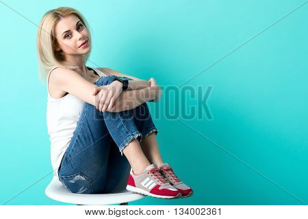 Portrait of pretty young woman having a seat on a chair. She is embracing legs with arms. The lady is looking at camera shyly. Isolated and copy space in right side