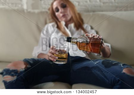 blond sad and wasted alcoholic drunk woman sitting at home sofa couch drinking and filling glass pouring scotch whiskey from bottle depressed and hangover in alcoholism and alcohol abuse