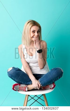 Cheerful blond girl is smiling while gossiping. She is sitting on chair with relaxation. The lady is looking at camera with surprise and covering mouth by arm shyly. Isolated on blue background