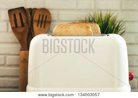 White toaster with toast cooked in the kitchen