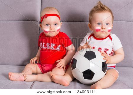 Soccer baby twins fans of Poland team in national colors