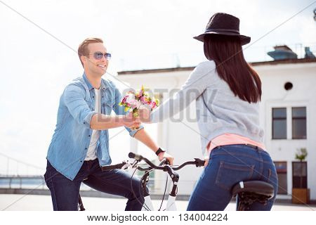 A little pleasure. Smiling energetic young man offering amazing flowers to a young woman while having a date on bikes